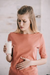 attractive woman with lactose intolerance looking at glass of milk