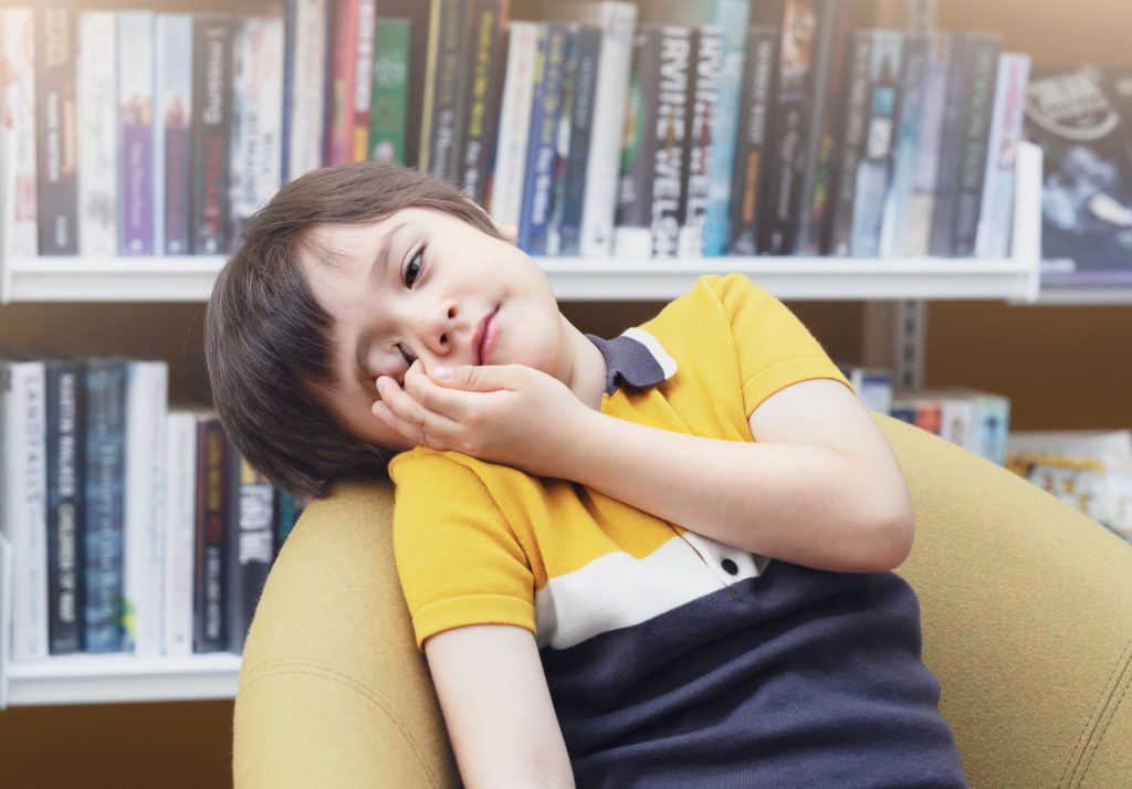 Tried boy rubbing his eyes while sitting in school library, bored kid fall asleep