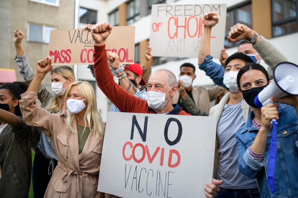 People with placards and posters on public demonstration, no covid vaccine concept
